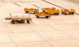 Empty transporting baggage trailer to airplane on runway. Royalty Free Stock Images
