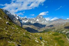 Lonely tourist walking in green alpine Aosta valley with Matterhorn on background