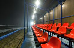 Empty tribune with rows wet red plastic seats on a football field. With snow and puddles. at night Royalty Free Stock Photography