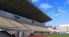 Empty tribunes on soccer stadium. Emty tribunes on a soccer stadium under bright sky Royalty Free Stock Photography