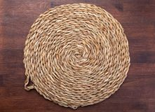 Empty trivet Of natural fibers. On dark wood background. Concept to include your food and your text royalty free stock photos