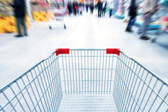 Empty trolley in supermarket. Or mall full of crowded people. Blur motion Royalty Free Stock Photo