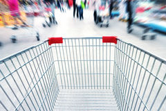 Empty trolley in supermarket. Or mall full of crowded people. Blur motion Stock Photos