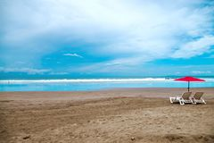 Empty tropical beach. Two beach chairs with a red umbrella on a tropical sand beach Stock Images