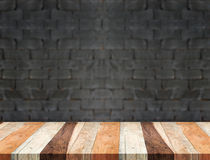 Empty tropical wood table and blurred black brick wall backgroun Royalty Free Stock Photo