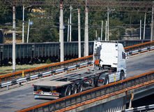 Empty truck on road, rides up over the bridge, industrial infrastructure and railroad in sea port, cargo transportation, delivery Stock Photography