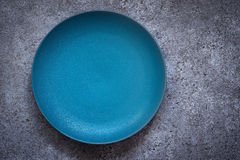 Empty turquoise ceramic plate On a concrete background. Top view. With copy space royalty free stock photography