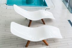 Empty two white lounge chairs inside of tiled room near swimming pool. Nobody in spa room. Deck chair for clients. Relaxation after spa procedures, bath house royalty free stock photo