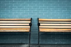 Empty two wooden bench on green brick wall background. Waiting for someone to full fill empty wooden chair. Brown wooden bench royalty free stock photo