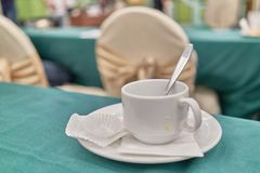Empty unclean white cup of coffee with spoon in conference Stock Photography