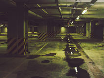 Empty underground parking garage. With burning lights and puddles Royalty Free Stock Photo