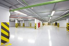 The empty underground parking place. Is located in a new modern building. It is safe clean and empty Stock Photography