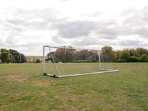 An Empty and Unused Goal Post with A White Net in the Middle of. A Park with Grass and Soil on the Ground, Wheels on the Frame to Help Move it and Houses and Stock Photos