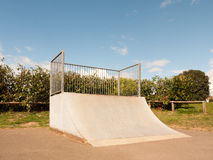 An Empty and Unused Ramp Half Pipe at the Skate Park in the Coun. Try Park in the UK Shining in the Sunlight of the Day and with A Shrub Hedge Behind the Bars Royalty Free Stock Images