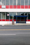 Empty urban city street, building and bus stop. An abstract vertical portrait of an empty, urban city street and bus stop shelter Stock Photos