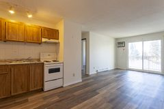 Empty Vacant Apartment Room. An empty vacant rental apartment property with new hardwood laminate floors and white paint on the walls royalty free stock photo