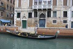 Empty venetian gondola in canal Royalty Free Stock Photography