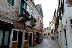 Empty Venetian street curves away from camera Royalty Free Stock Photography