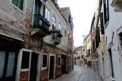 Empty Venetian street curves away from camera Royalty Free Stock Photography