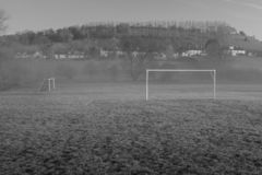 Empty village football field, small amount of fog drifting through. Hill in the back ground with houses stock image