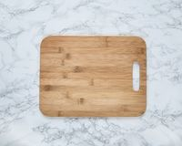 Empty vintage cutting board on a marble background.  royalty free stock images