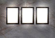 Empty,vintage gallery frames. 3 empty picture frames with spotlights against a marble wall, design template, free copy space Stock Photos