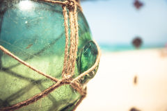 Empty vintage glass jar with rope on tropical beach with blurred background and copy space. Vintage glass jar with rope on tropical beach with blurred background Royalty Free Stock Photos
