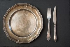 Empty vintage metal plate with silverware on black, with copy space for your menu or recipe. Menu card for restaurants. Table plase setting Royalty Free Stock Image