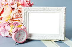 Empty vintage photo frame and pink alarm clock. Royalty Free Stock Images