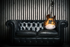 Empty vintage sofa and electric guitar with modern wood wall recording studio background. Music concept with nobody Stock Photo