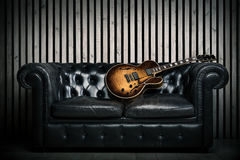 Empty vintage sofa and electric guitar with modern wood wall recording studio background. Music concept with nobody.  Stock Images
