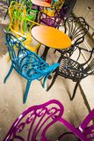 Empty vintage terrace in historical downtown with multi-colored chairs on the pavement sidewalk. Colorful chairs in retro stock photos
