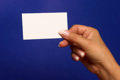 Empty visiting-card in palm. On blue background Stock Photos