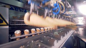 Empty wafer cones are being put into a factory machine while cones filled with cream are getting displaced from one. Conveyor onto another one. 4K stock video