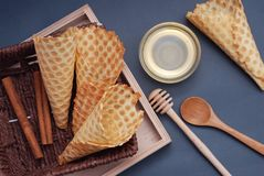 Empty waffle cones Homemade Dessert with wooden Accesories and honney. Blue Background. Top view stock image