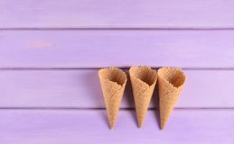 Empty waffle horns on a violet wooden background. Pastel color trend, minimalist, top view. Empty waffle horns on a violet wooden background. Pastel color trend royalty free stock photography