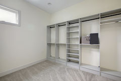 Empty walk-in closet with open shelves. And grey carpet floor. Northwest, USA royalty free stock photo