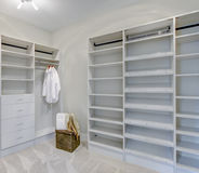 Empty walk-in closet with open shelves. And grey carpet floor. Northwest, USA stock photo