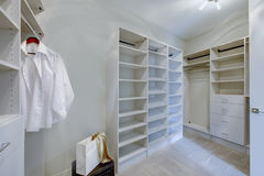 Empty walk-in closet with open shelves. And grey carpet floor. Northwest, USA royalty free stock photography