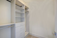 Empty walk-in closet with open shelves. And grey carpet floor. Northwest, USA stock photography