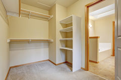 Empty walk-in closet with wood shelves, beige carpet floor. Bright empty walk-in closet with wood shelves, beige carpet floor stock images