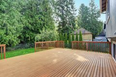 Empty walkout deck with redwood railings. Empty walkout deck boasts redwood railings overlooking well kept back yard stock photos