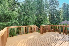 Empty walkout deck with redwood railings. Empty upper level deck boasts redwood railings overlooking the lower level deck Royalty Free Stock Photo