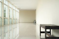 Empty walkway in building hall perspective with long white wall. On right side and long windows with light on left and granito tiles floor in minimalist Stock Image