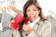 Empty wallet - woman with no money shopping. Empty wallet - woman with no money in purse shopping. Female shopper in clothes store upset crying as she is out of Stock Images