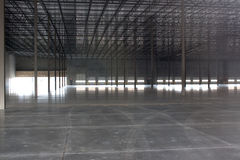 Empty Warehouse. New warehouse space left empty by the economic downturn. Image shows the inside of the building with bare, empty floor and loading bay doors royalty free stock image