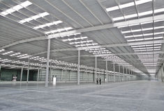 Empty warehouse with human figures