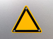 Empty warning sign on a metal surface. Empty warning sign (template) on a metal surface with space for sign, logo, symbol and text Royalty Free Stock Images