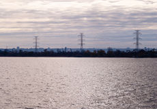 Empty water against power lines and cloudy sky Royalty Free Stock Photography