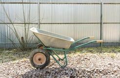 Empty wheelbarrow on the garden plot is on the rubble royalty free stock images
